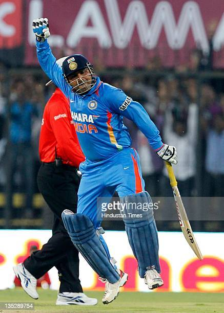 Virender Sehwag of India pumps his fist in joy after scoring a double hundred during the 4th One Day International between India and West Indies at...