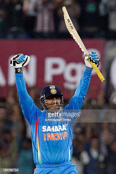 Virender Sehwag of India raises his bat after scoring a double hundred during the 4th One Day International between India and West Indies at Holkar...