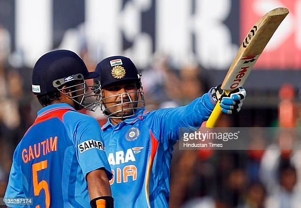 Virender Sehwag of India raises his bat after scoring a halfcentury as teammate Gautam Gambhir congratulates him during the 4th One Day International...