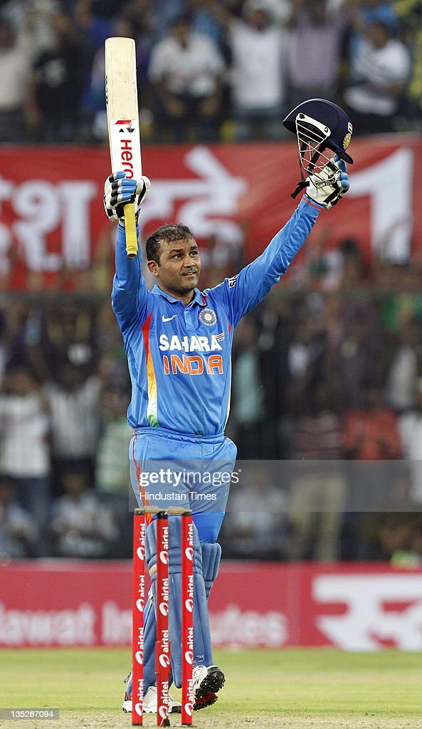 <a gi-track='captionPersonalityLinkClicked' href=/galleries/search?phrase=Virender+Sehwag&family=editorial&specificpeople=176591 ng-click='$event.stopPropagation()'>Virender Sehwag</a> of India raises his bat and helmet after scoring a double hundred during the 4th One Day International between India and West Indies at Holkar Stadium in Indore, India on December 8, 2011.