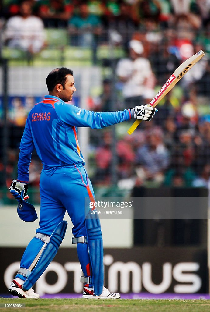<a gi-track='captionPersonalityLinkClicked' href=/galleries/search?phrase=Virender+Sehwag&family=editorial&specificpeople=176591 ng-click='$event.stopPropagation()'>Virender Sehwag</a> of India raises his bat on reaching his century during the opening game of the ICC Cricket World Cup between Bangladesh and India at the Shere-e-Bangla National Stadium on February 19, 2011 in Dhaka, Bangladesh.