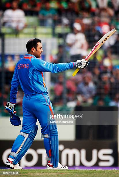 Virender Sehwag of India raises his bat on reaching his century during the opening game of the ICC Cricket World Cup between Bangladesh and India at...