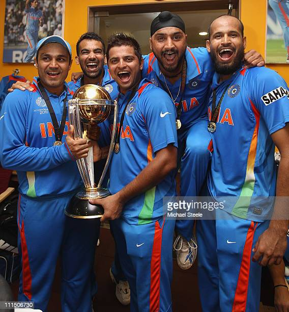 Virender Sehwag Zaheer Khan Suresh Raina Harbhajan Singh and Yusuf Pathan pose with the world cup trophy in the players dressing room after their six...