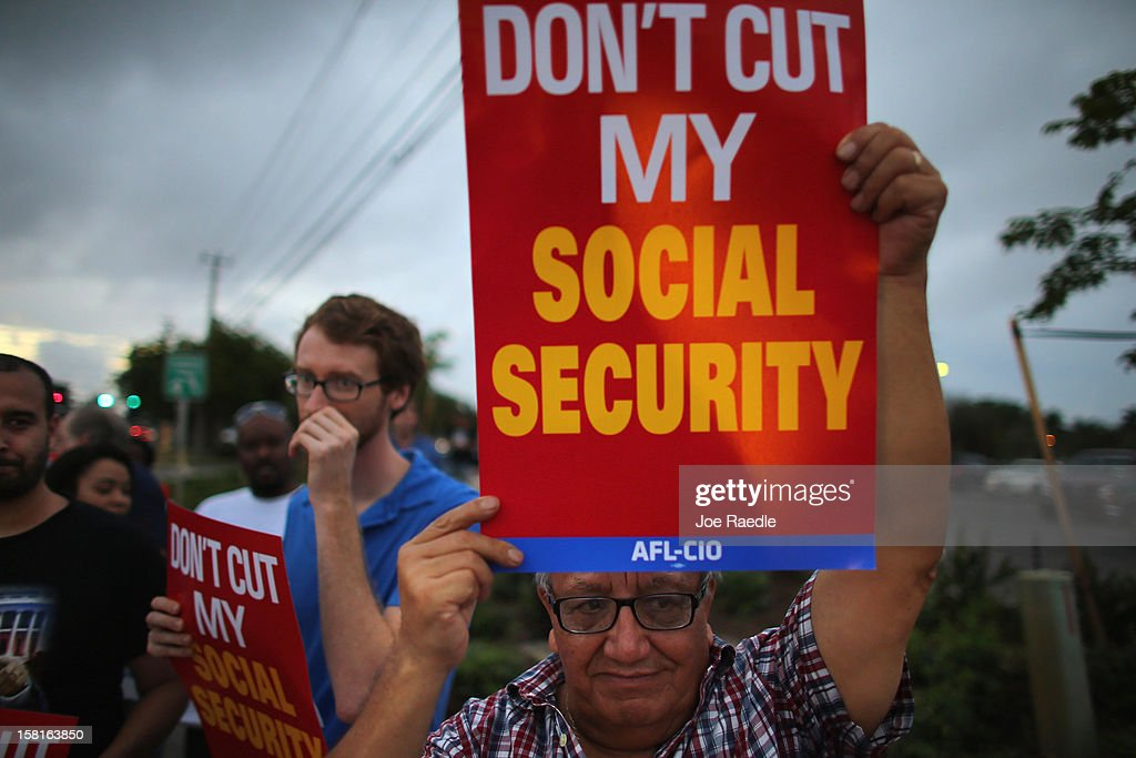 Virgilio Marquina and other protesters rally together outside the office of U.S. Sen. Marco Rubio (R-FL) on December 10, 2012 in Doral, Florida. The protesters are hoping that Senators like Rubio will not cut medicare/social security benefits and will agree to raise taxes on the top 2% of earners in the country.