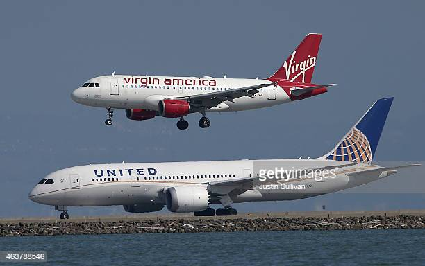 Virgin America plane lands above a United Airlines plane at San Francisco International Airport on February 18 2015 in San Francisco California...