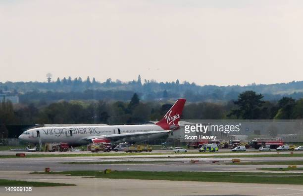 Virgin Atlantic aircraft stands on the tarmac with emergency service vehicles in support after making an emergency landing at Gatwick Airport on...