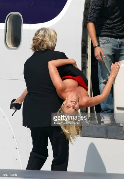 Virgin Atlantic boss Sir Richard Branson carries model Kate Moss on a wing of a jumbo jet at Heathrow Airport on June 22 2009 in London England Today...