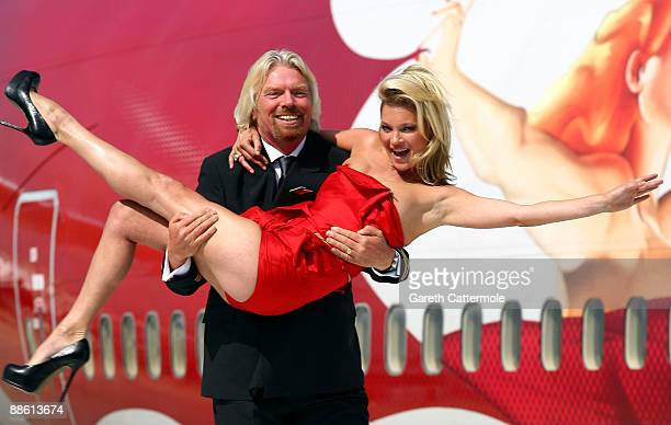 Virgin Atlantic boss Sir Richard Branson poses with model Kate Moss on a wing of a jumbo jet at Heathrow Airport on June 22 2009 in London England...