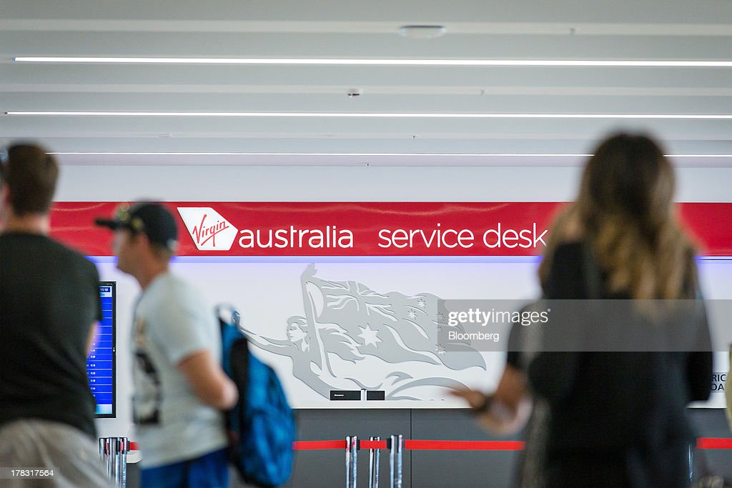 Virgin Australia Holdings Ltd. signage is displayed at a service desk at the domestic terminal of Sydney Airport in Sydney, Australia, on Thursday, Aug. 29, 2013. Virgin will make a net loss in the range of A$95 million to A$110 million when it reports annual results tomorrow, the Brisbane-based carrier forecast Aug. 5. Photographer: Ian Waldie/Bloomberg via Getty Images