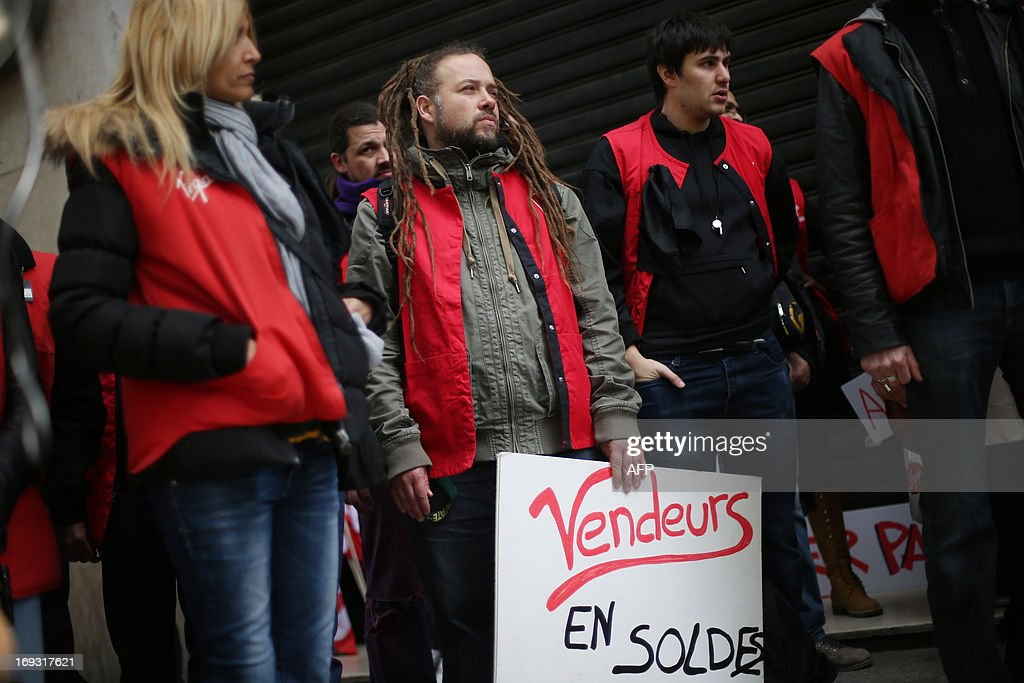 A Virgin employee holds a sign reading 'Workers for sale' as he takes part in a demonstration in defense of workers' jobs in front of the Virgin megastore on the Champs-Elysees in Paris, on May 23, 2013. As disgruntled workers continue to protest in front of stores across France the court currently overseeing the closing of the Virgin megastore in Paris declared on May 22 that the deadline for applications for the store to be reopened by another company could be pushed back to allow more prospective buyers to make offers.