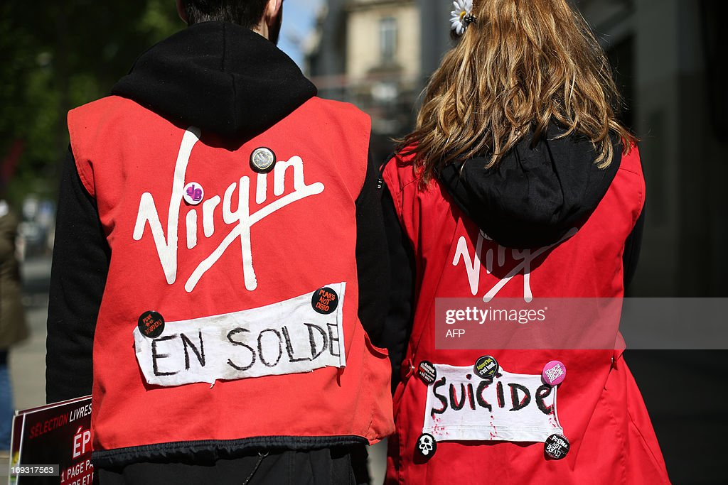 Virgin employees put rags on their work vests bearing the words 'Discount' and 'Suicide' as they take part in a demonstration in defense of workers' jobs in front of the Virgin megastore on the Champs-Elysees in Paris, on May 23, 2013. As disgruntled workers continue to protest in front of stores across France the court currently overseeing the closing of the Virgin megastore in Paris declared on May 22 that the deadline for applications for the store to be reopened by another company could be pushed back to allow more prospective buyers to make offers.