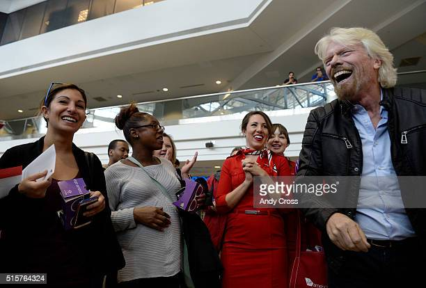 Virgin Group Founder Sir Richard Branson right has a laugh with air traveler Melissa Moreno left after Branson handed her free round trip tickets to...