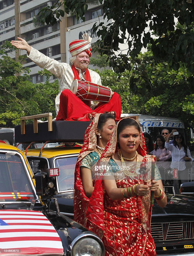 Virgin Group's Sir Richard Branson sitting on top of a black-and-yellow city taxi, plays a traditional Indian drum during a photo opportunity parade in Nariman point on October 26, 2012 in Mumbai, India. Virgin Atlantic is re-launching its Mumbai-London flight from Sunday after a three-year gap.