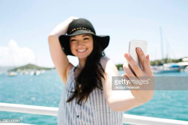 USA, Virgin Islands, Saint Thomas, Woman doing selfie with bay in background