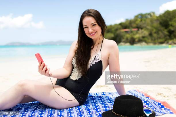 USA, Virgin Islands, Saint Thomas, Woman listening to music on beach during summer vacations
