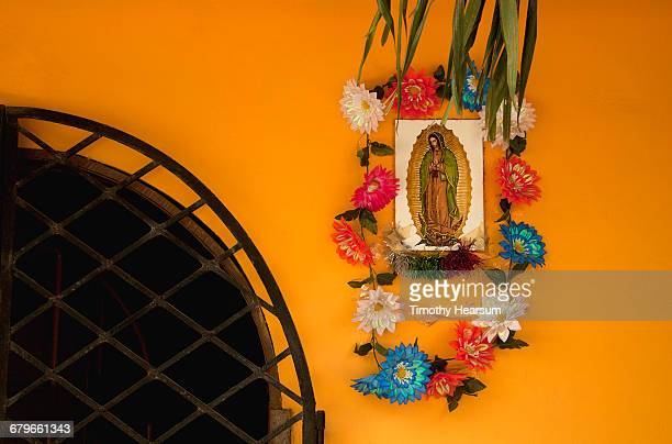 Virgin Mary plaque with flowers on colorful wall