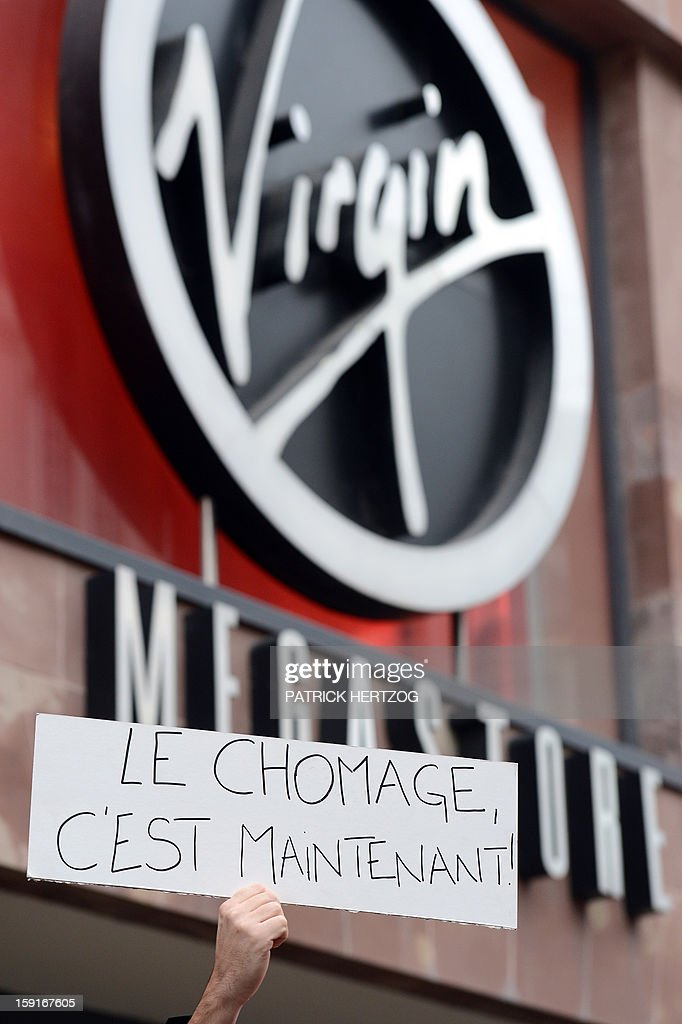 A Virgin Megastore employee holds a sign reading 'Unemployment, it's now' during a demonstration against planned job cuts at the entrance of the store on January 9, 2013 in Strasbourg, eastern France. Virgin's Megastore music and book unit, which is known in France as a 'culture' retailer, said it will file for insolvency on January 9, 2013. Originally started by Richard Branson, the British billionaire and chairman of the Virgin Group, the Virgin Megastores were bought by the French Lagardere group in 2001. AFP PHOTO / PATRICK HERTZOG
