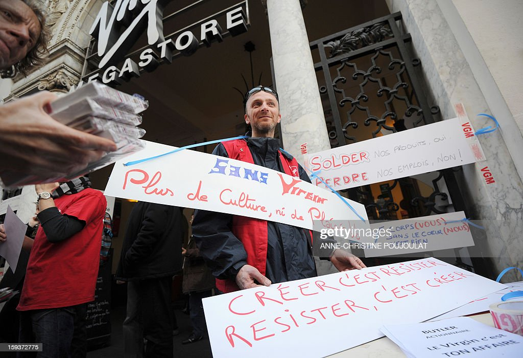 A Virgin Megastore employee wears a sign reading in French 'Without Virgin, no Culture, nor Pleasure' during a demonstration against planned job cuts at the entrance of the store in Marseille, southeastern France, on January 12, 2013. Entertainment retailer Virgin France filed officially for bankruptcy on January 9 after becoming the latest victim of consumers shifting to buying digital music and video.