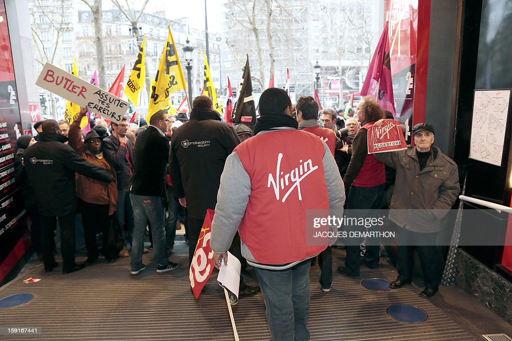 Virgin Megastore employees demonstrate against planned job cuts at the entrance of the store on the Champs-Elysees avenue on January 9, 2013 in Paris. Virgin's Megastore music and book unit, which is known in France as a 'culture' retailer, said it will file for insolvency on January 9, 2013, and is the latest to leave the Champs as clothing chains, luxury goods shops and automobile showrooms take over. Originally started by Richard Branson, the British billionaire and chairman of the Virgin Group, the Virgin Megastores were bought by the French Lagardere group in 2001. AFP PHOTO/JACQUES DEMARTHON