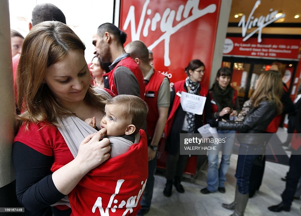 Virgin Megastore employees demonstrate against planned job cuts at the entrance of a Virgin Megastore on January 9, 2013 in Nice, southern France. Virgin's Megastore music and book unit, which is known in France as a 'culture' retailer, said it will file for insolvency on January 9, 2013. Originally started by Richard Branson, the British billionaire and chairman of the Virgin Group, the Virgin Megastores were bought by the French Lagardere group in 2001. AFP PHOTO VALERY HACHE