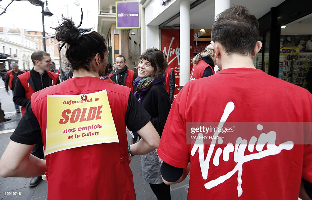 Virgin Megastore employees demonstrate against planned job cuts at the entrance of the store on January 9, 2013, in Nice, southeastern France. Virgin's Megastore music and book unit, which is known in France as a 'culture' retailer, said it will file for insolvency on January 9, 2013. Originally started by Richard Branson, the British billionaire and chairman of the Virgin Group, the Virgin Megastores were bought by the French Lagardere group in 2001. Placard hung on an employee's jacket at left reads : 'Sale on our jobs and on culture today'. HACHE