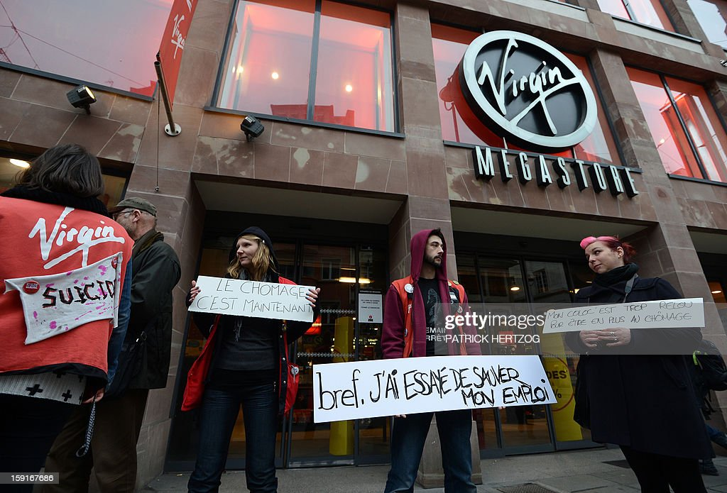 Virgin Megastore employees demonstrate against planned job cuts at the entrance of the store on January 9, 2013 in Strasbourg, eastern France. Virgin's Megastore music and book unit, which is known in France as a 'culture' retailer, said it will file for insolvency on January 9, 2013. Originally started by Richard Branson, the British billionaire and chairman of the Virgin Group, the Virgin Megastores were bought by the French Lagardere group in 2001. AFP PHOTO / PATRICK HERTZOG