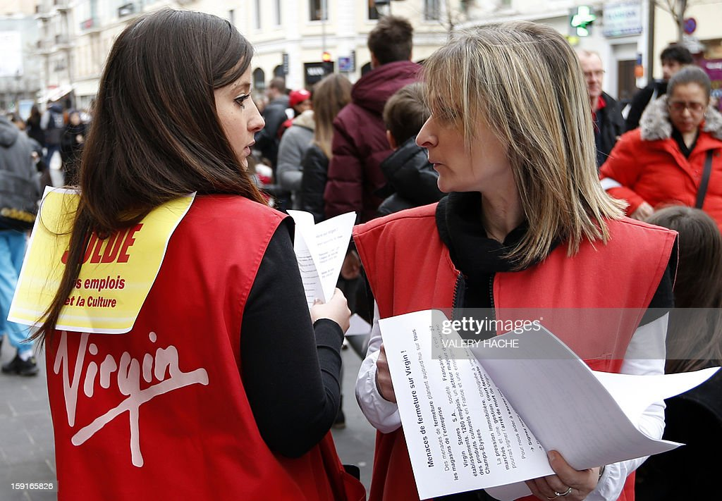 Virgin Megastore employees distribute trade union leaflets as they demonstrate against planned job cuts at the entrance of the store on January 9, 2013, in Nice, southeastern France. Virgin's Megastore music and book unit, which is known in France as a 'culture' retailer, said it will file for insolvency on January 9, 2013. Originally started by Richard Branson, the British billionaire and chairman of the Virgin Group, the Virgin Megastores were bought by the French Lagardere group in 2001.