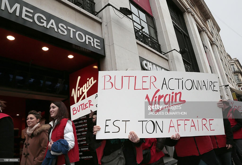 Virgin Megastore employees hold a sign reading 'Butler shareholder, Virgin is your business' (Butler actionnaire, Virgin est ton affaire) as they demonstrate against planned job cuts at the entrance of the store on the Champs-Elysees avenue on January 9, 2013 in Paris. Virgin's Megastore music and book unit, which is known in France as a 'culture' retailer, said it will file for insolvency on January 9, 2013, and is the latest to leave the Champs as clothing chains, luxury goods shops and automobile showrooms take over. Originally started by Richard Branson, the British billionaire and chairman of the Virgin Group, the Virgin Megastores were bought by the French Lagardere group in 2001.