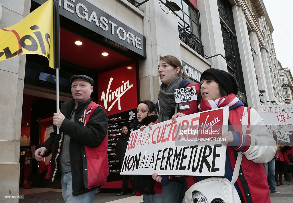 Virgin Megastore employees hold a sign reading 'Yes to culture, no to closure' (Oui à la culture, non à la fermeture) as they demonstrate against planned job cuts at the entrance of the store on the Champs-Elysees avenue on January 9, 2013 in Paris. Virgin's Megastore music and book unit, which is known in France as a 'culture' retailer, said it will file for insolvency on January 9, 2013, and is the latest to leave the Champs as clothing chains, luxury goods shops and automobile showrooms take over. Originally started by Richard Branson, the British billionaire and chairman of the Virgin Group, the Virgin Megastores were bought by the French Lagardere group in 2001.