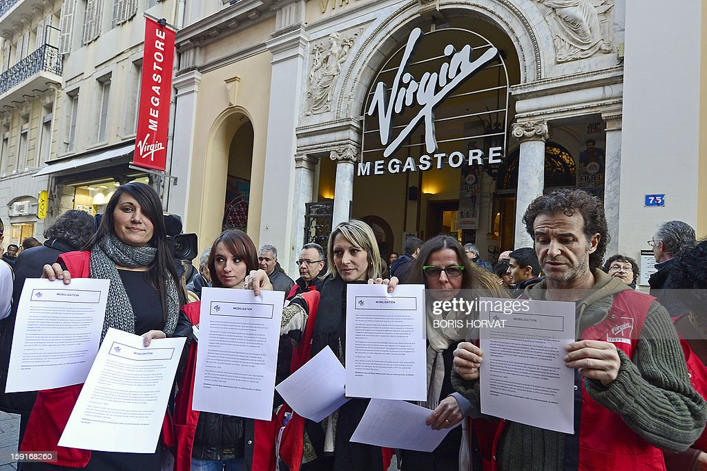 Virgin Megastore employees hold pamphlets during a demonstration against planned job cuts at the entrance of the store on January 9, 2013 in Marseille, eastern France. Virgin's Megastore music and book unit, which is known in France as a 'culture' retailer, said it will file for insolvency on January 9, 2013. Originally started by Richard Branson, the British billionaire and chairman of the Virgin Group, the Virgin Megastores were bought by the French Lagardere group in 2001.
