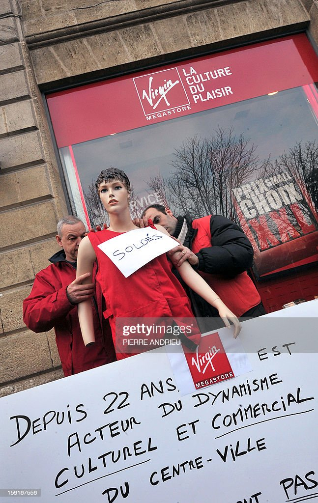 Virgin Megastore employees install a mannequin during a demonstration against planned job cuts at the entrance of a Virgin Megastore on January 9, 2013 in Bordeaux, southwestern France. Virgin's Megastore music and book unit, which is known in France as a 'culture' retailer, said it will file for insolvency on January 9, 2013. Originally started by Richard Branson, the British billionaire and chairman of the Virgin Group, the Virgin Megastores were bought by the French Lagardere group in 2001.