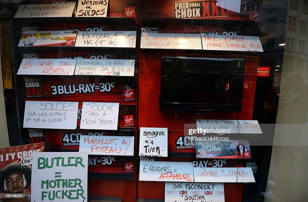 Virgin Megastore employees leave signs in the store's window display as they demonstrate against planned job cuts at the entrance of the store on January 9, 2013 in Strasbourg, eastern France. Virgin's Megastore music and book unit, which is known in France as a 'culture' retailer, said it will file for insolvency on January 9, 2013. Originally started by Richard Branson, the British billionaire and chairman of the Virgin Group, the Virgin Megastores were bought by the French Lagardere group in 2001. AFP PHOTO / PATRICK HERTZOG