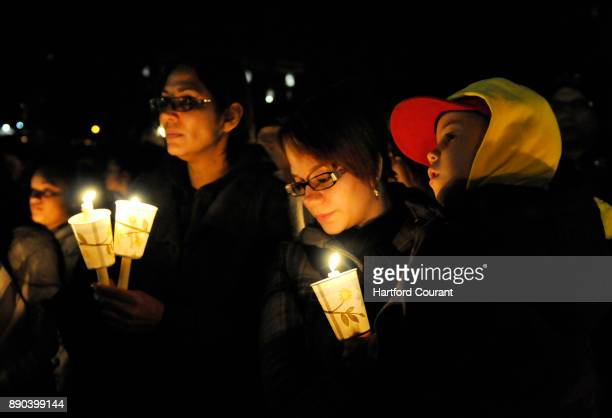Virgin Rodriguez second from right holds her son Elias during a candlelight vigil at Hartford Connecticut's Bushnell Park on Friday December 14 to...