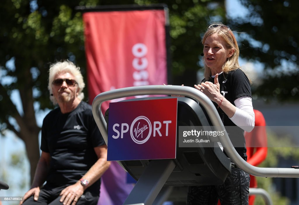 Virgin Sport CEO Mary Wittenberg (R) speaks during a news conference to announce the launch of Virgin Sport as Sir Richard Branson (L) watches on May 18, 2017 in San Francisco, California. Virgin Group founder Sir Richard Branson announced Virgin Sport San Francisco, a half marathon run and fitness festival that is scheduled for October 14.