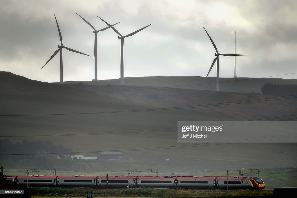 A Virgin train passes along the West Coast mainline route near Abington, as wind turbines stand in the distance on August 29, 2012 in Scotland. Earlier this month Virgin lost out to First Group in their bid to run a 13 year West Coast franchise starting in December and are now starting a legal challenge to try and maintain the service it has operated for the past 15 years.