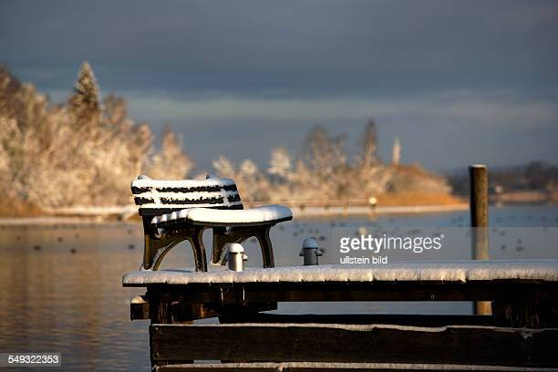 Virgin winter snow on bench seat and old wooden pier Chiemsee Chiemgau Upper Bavaria Germany