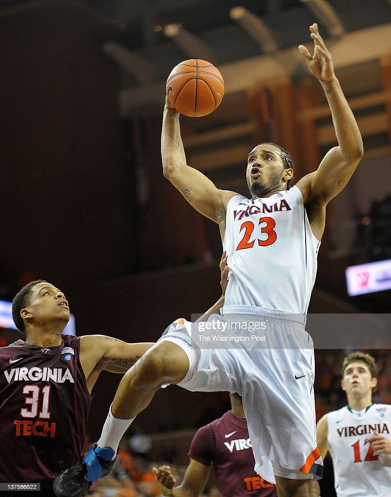 Virginia Cavaliers forward Mike Scott center flys throught air againstVirginia Tech Hokies guard/forward Jarell Eddie left for a 2nd half dunk as the...