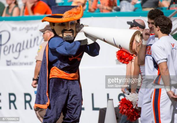 Virginia Cavaliers mascot Cavalier listens to a Virginia cheerleader with her megaphone on the field before the start of the college football game...