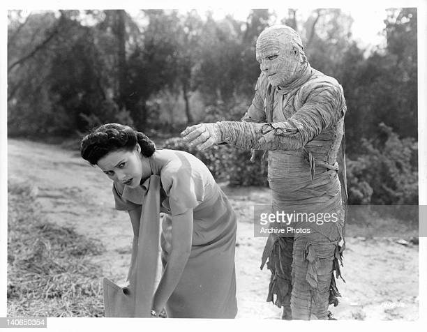 Virginia Christine bends over as Lon Chaney Jr walks up behind her to grab her as a mummy in a scene from the film 'The Mummy's Curse' 1944