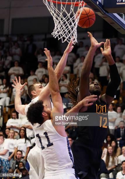 Virginia Commonwealth Rams forward Mo AlieCox takes a shot over George Washington Colonials forward Arnaldo Toro during a college basketball game...