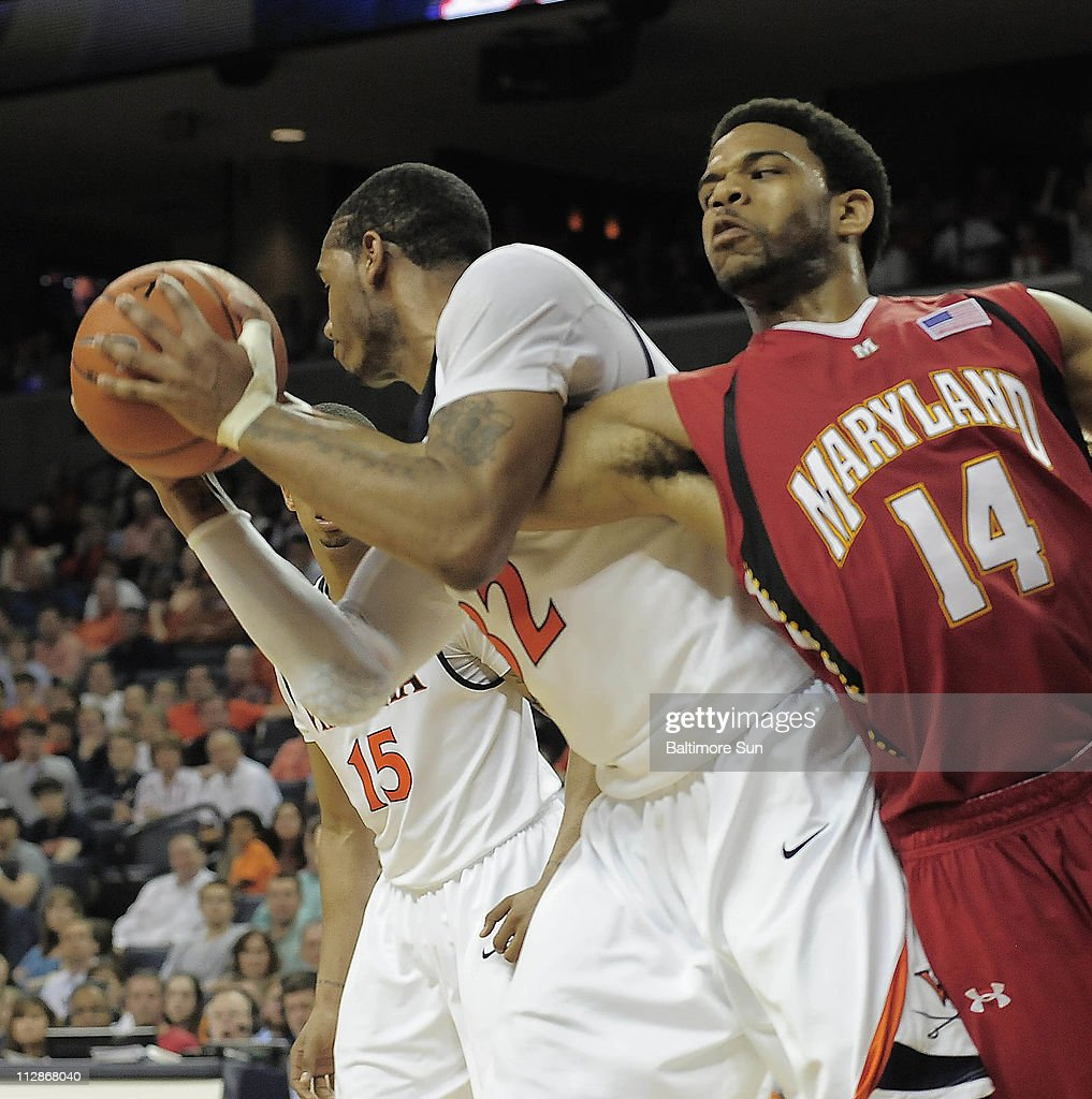 Virginia forward Mike Scott grabs the arm of Maryland guard/forward Sean Mosley while hauling in a rebound in the second half at John Paul Jones...