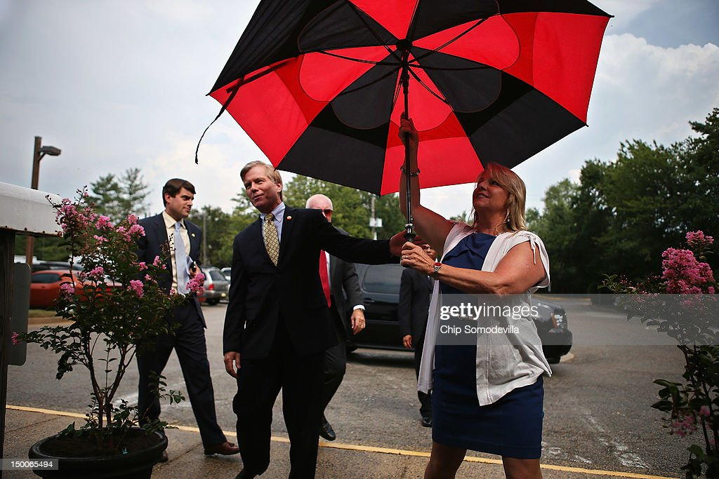 Virginia Gov. Bob McDonnell and his wife Maureen McDonnell (R) take shelter from a brief summer rain storm as they arrive for a tour of the KinderCare Learning Center August 9, 2012 in Alexandria, Virginia. A 21-year veteran of the U.S. Army, Gov. McDonnell's visit to the center is part of KinderCare's Honoring the Troops program taking place at the end of August in Virginia and Maryland.