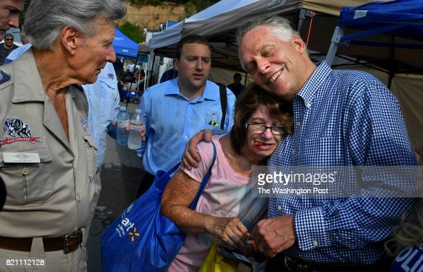 Virginia Gov Governor Terry McAuliffe gives a hug to Patricia McConnell who saved money for 6 months to attend the Remote Area Medical event to get...