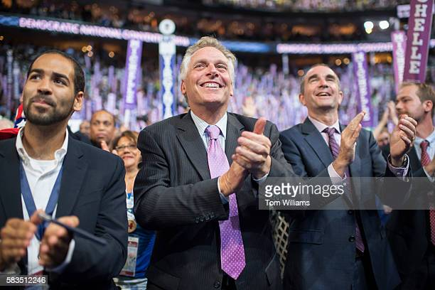 Virginia Gov Terry McAuliffe center and Lt Gov Ralph Northam right cheer on the floor of the Wells Fargo Center in Philadelphia Pa on the first day...