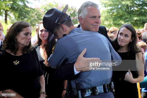 Virginia Governor Terry McAuliffe is embraced by a Virginia State Police trooper after he and his wife Dorothy McAuliffe attended the funeral for...