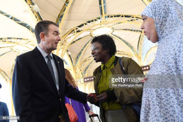 Virginia Lieutenant Governor Ralph Northam left talks to Esther Nchom center while Rabia Khatoon right looks on as Northam visits airport workers at...