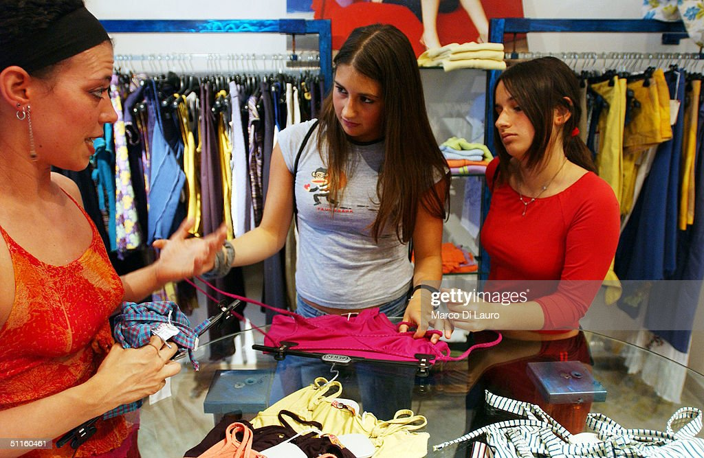 Virginia Recchi, 16, (L) and Ludovica Lombardini, 17, (R) shop for cloths June 18, 2004 in Rome, Italy. In Rome privileged teenagers get around mainly in very expensive small cars for which they don't need a license plate or a driver's license. They all dress in the same metropolitan style, and spend most of their free time wandering around not doing much. Many teenagers' status symbols are cloths, mobile phone and accessories. Most of them have credit cards and act as if they are adults.