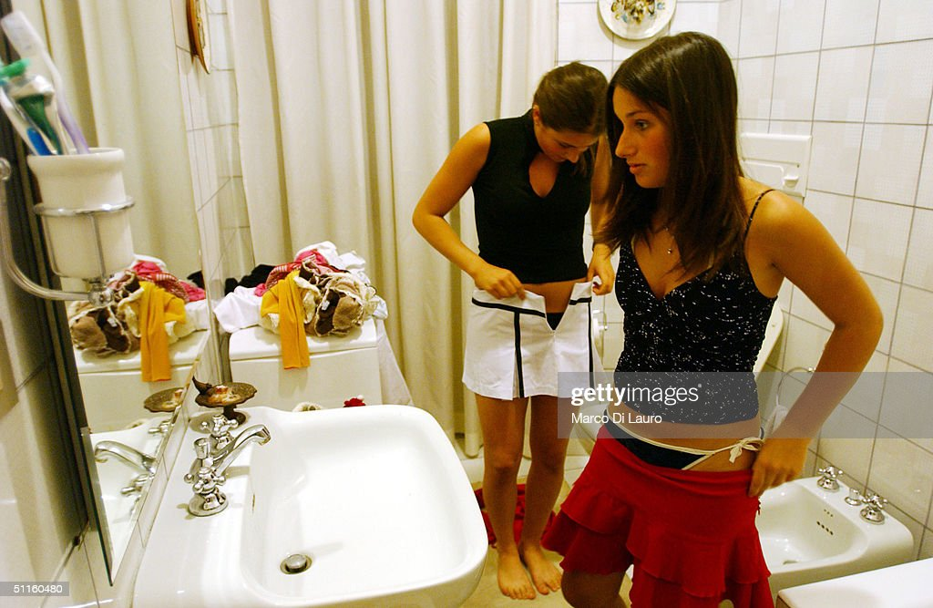 Virginia Recchi, 16, (R) and Ludovica Lombardini, 17, (L) try to decide what to wear in Ludovica's bathroom before going to a party June 19, 2004 in Rome, Italy. In Rome privileged teenagers get around mainly in very expensive small cars for which they don't need a license plate or a driver's license. They all dress in the same metropolitan style, and spend most of their free time wandering around not doing much. Many teenagers' status symbols are cloths, mobile phone and accessories. Most of them have credit cards and act as if they are adults.