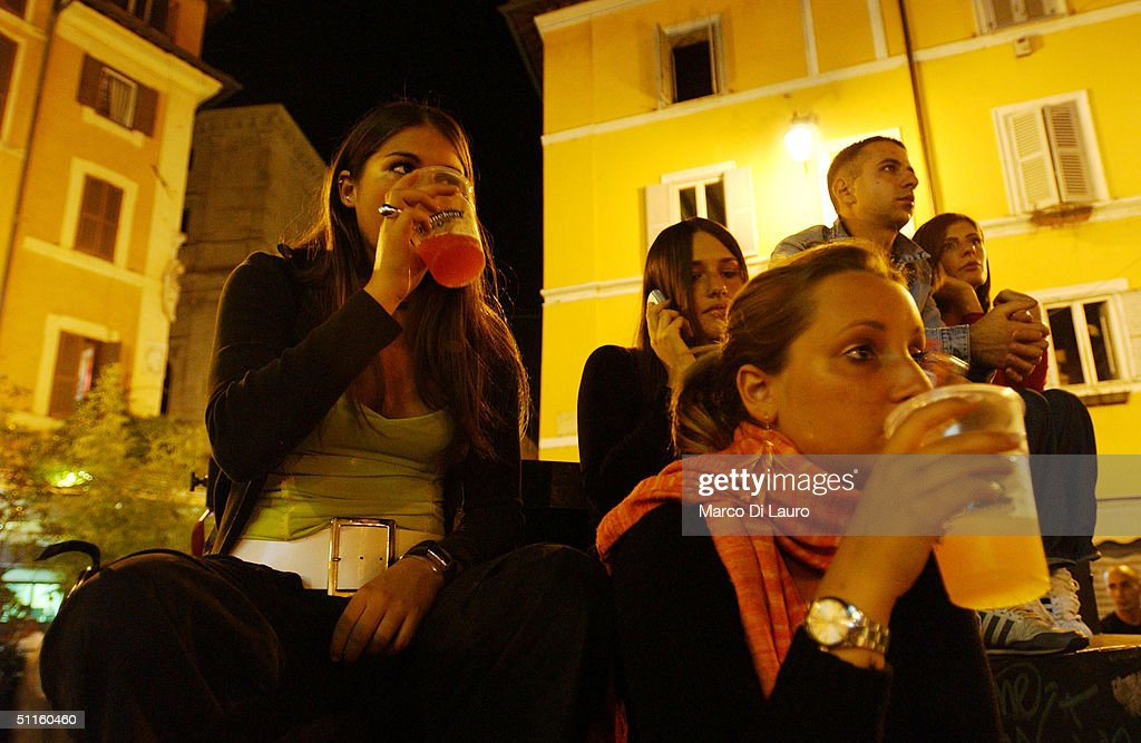 Virginia Recchi, 16, Violante Pasolini, 17, (front C) and Ludovica Lombardini, 17, sit as they have a drink in a square June 17, 2004 in Rome, Italy. In Rome privileged teenagers get around mainly in very expensive small cars for which they don't need a license plate or a driver's license. They all dress in the same metropolitan style, and spend most of their free time wandering around not doing much. Many teenagers' status symbols are cloths, mobile phone and accessories. Most of them have credit cards and act as if they are adults.