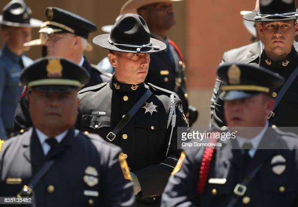 Virginia State Police and other law enforcement officers wait outside Saint Paul's Baptist Church following TrooperPilot Berke MM Bates's funeral...
